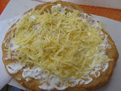 hungarian langos.. this stuff is amazing - it's basically fried bread, with sour cream and grated cheese. yum