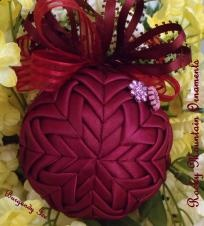 Burgundy Ice Quilted Ornament  This 3 inch ornament is layered in the star pattern with burgundy satin ribbon. The top is embellished with burgundy satin ribbon.Attached is a crystal burgundy charm, The side is embellished with burgundy crystals. This ornaments comes gift boxed. Price: $25.00