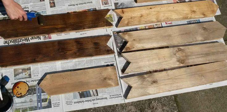 Auf Zeitung liegende Holzpfeile für einen Wegweiser, die mit brauner Farbe gestrichen werden.