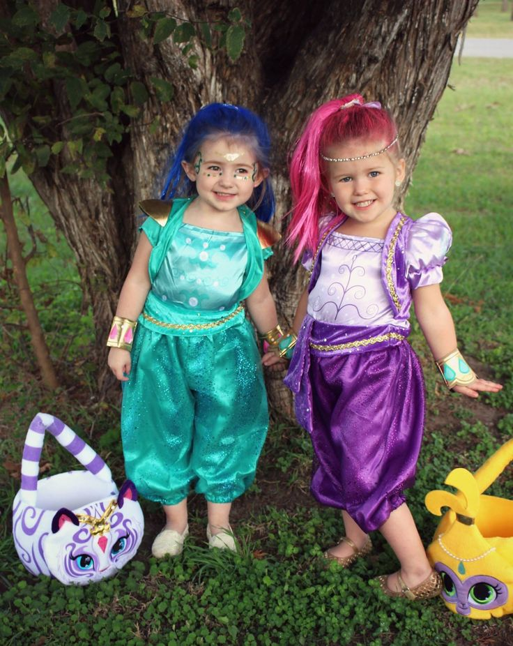 """Shimmer and Shine Halloween costume idea!! Also perfect for a themed birthday party.  We got both of these costumes at Walmart, the hair piece and armbands were included! We found the plush trick-or-treat buckets at Spirit Halloween. (We sprayed their natural hair with the color spray also from Walmart, the headband on """"Shimmer"""" was just an old necklace, and the face tattoos on """"Shine"""" were also from Spirit Halloween."""