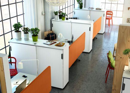 Un ufficio con scrivanie e mobili bianchi e schermi divisori arancioni GALANT