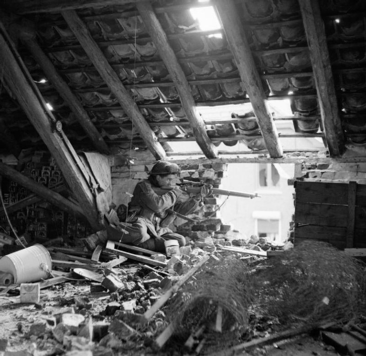 """A sniper from """"C"""" Company, 5th Battalion, The Black Watch, 51st (Highland) Division, in position in the loft space of a ruined building in Gennep, Holland, 14 February 1945."""