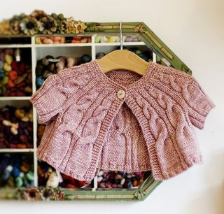 An adorable unisex baby cardigan using engineered cables to give it a wonderful shape. Knit from the top down with just one skein (100g) of yarn. Materials: Yarn: One skein of The Uncommon Thread DK (100% superwash Blue Faced Leicester, 225m/100g). Any good DK yarn can be substituted. Needles: 3.75mm (UK 9/US 5) Notions: Cable needle, 2 pieces of waste yarn and one button. Tension: 22