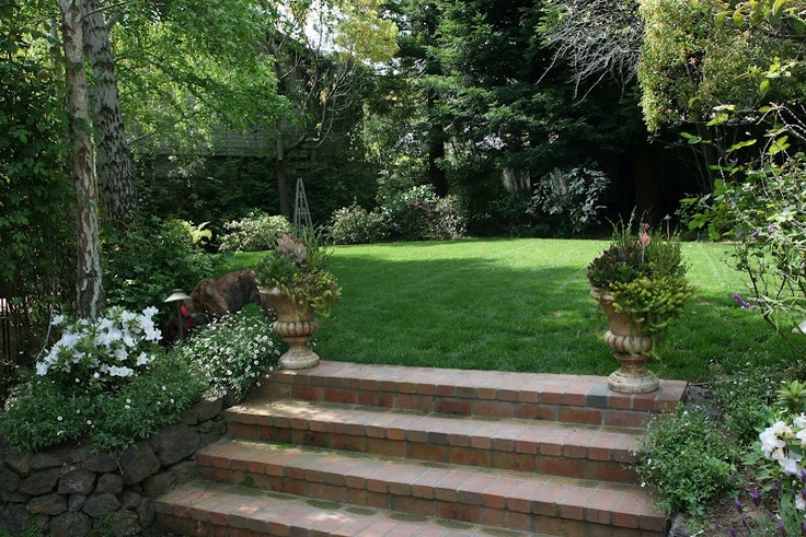 Brick steps. Grass. Privacy. Blooming beds. Containers.
