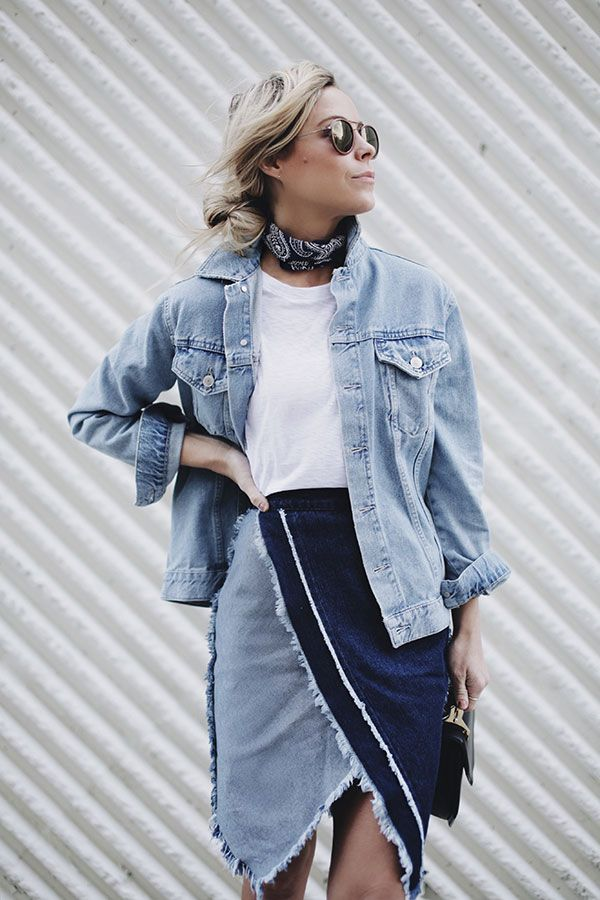 Street style look com jaqueta jeans, camiseta branca, saia assimétrica jeans.