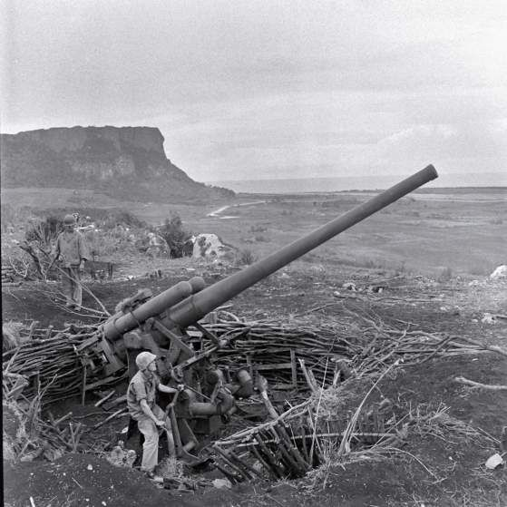 <b>Unpublished. </b>A crew maneuvers an enormous piece of artillery during the Battle of Saipan, 1944. In the waning days of the struggle for the island, thousands of Japanese civilians and troops committed suicide, rather than surrender to American troops. Many leapt to their death from the top of sheer cliffs that fall 200 feet to rocks and surf below.