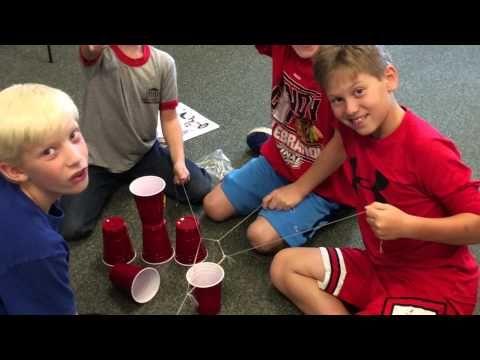 Samenwerkopdracht. Elastiek met voor ieder kind een touwtje eraan. Samen de bekers optillen en een toren maken. AK