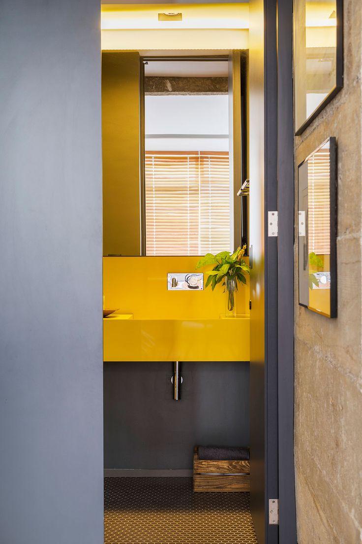 Decoração de apartamento com concreto no banheiro amarelo, lavabo amarelo, plantas na decoração, parede cinza.