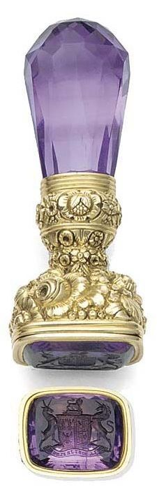 An early 19th century gold-cased and amethyst locket desk seal, with faceted amethyst handle, the mount chased and engraved with flower sprays and garland top with reeded border, the foiled amethyst matrix engraved with the arms of the Lennox family