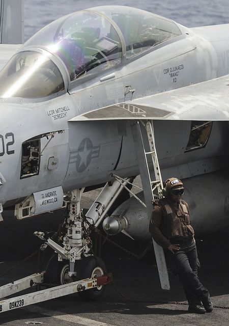 """RED SEA (Sept. 3, 2013) Airman Carlton O'Neal, assigned to the """"Black Knights"""" of Strike Fighter Squadron (VFA) 154, rests for a moment next to a F/A-18F Super Hornet on board the aircraft carrier USS Nimitz (CVN 68). (U.S. Navy photo by Mass Communication Specialist 3rd Class Phil Ladouceur/Released)"""