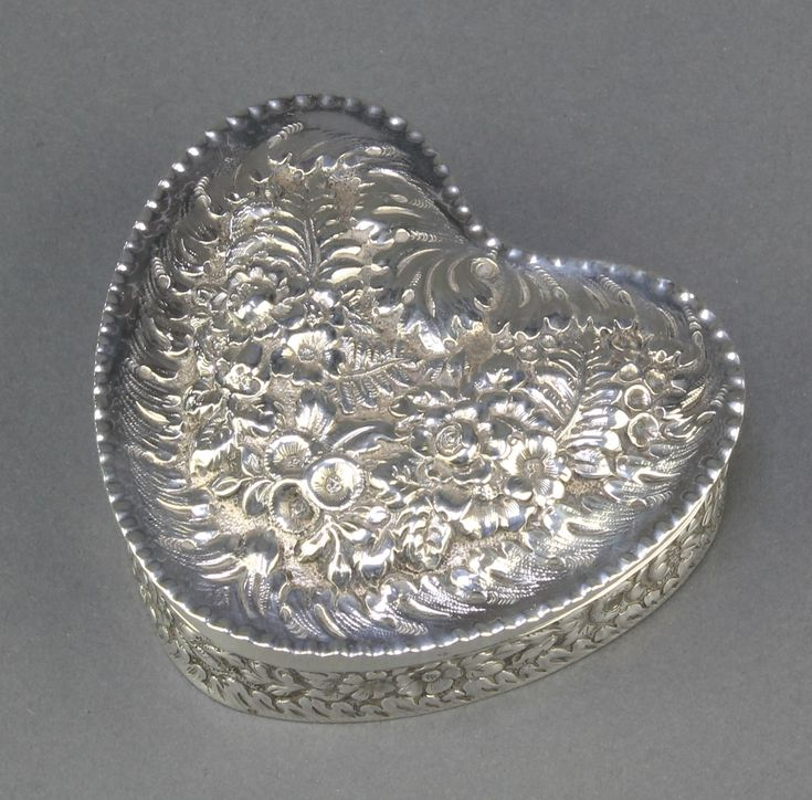 """Lot 527, A Tiffany Sterling silver heart shaped trinket box  with floral decoration 140 grams 3 1/2"""", Est £80-120"""