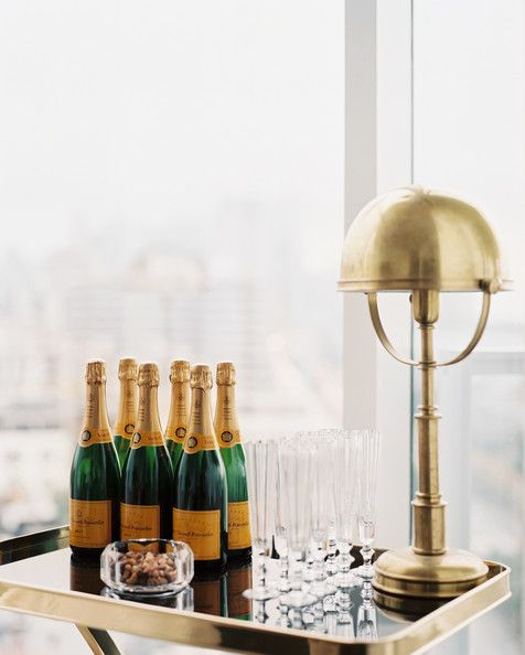 Champagne, glassware, and a brass lamp on a tray table
