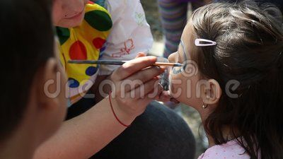 Artist paints on children's faces in Cismigiu park, Bucharest, Romania.