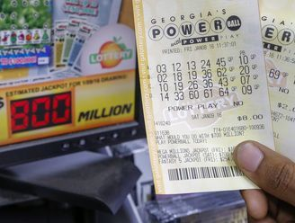 A customer shows his tickets for the multi-state Powerball lottery jackpot, the largest in U.S. history, at a convenience store in Madison, Ga., on Jan. 8, 2016.