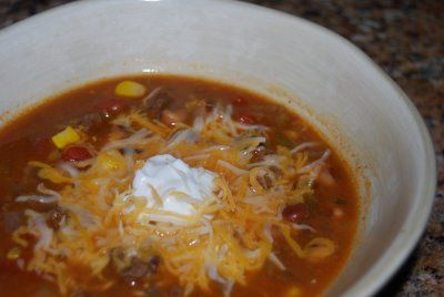 Taco Soup  Ingredients:  1 lb. extra lean ground beef  1 chopped onion  1 packet ranch dressing mix  1 packet taco seasoning mix  1 can rotel tomatoes (original blend)  1 can whole kernal corn (don't drain)  1 can chili beans (don't drain)  1 can black beans (drain and rinse)  For Topping:  2 % shredded mexican cheese blend  Fat Free Sour Cream  Baked Tortilla Chips  Directions:  Brown ground beef together with onion, ranch mix, and taco mix in a large skillet. In a large pot, add rotel…