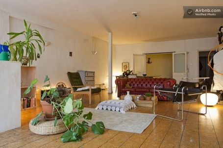 Living Loft with Red Three Cushions Armchair and Wooden and Steel Single Armchairs and White Rug and Wooden Deck Flooring in Studio Apartmen...