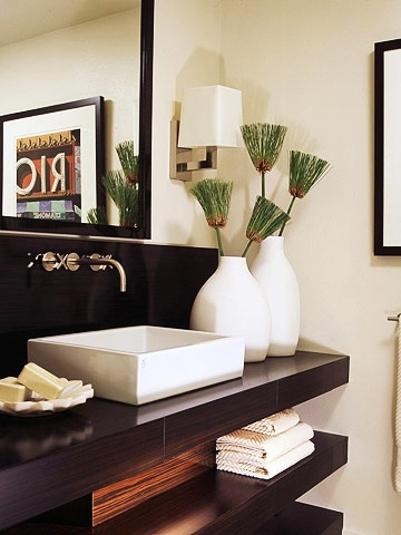 A clever use of contrast can add drama to even the tiniest space. Here, an ebony vanity makes a striking statement against creamy neutral walls and accessories. Boxy sconces echo the shape of the vanilla sink and the sheen of the stainless-steel fixtures. The shelves below, which are ideal for displaying towels, smartly incorporate shallow drawers for toiletries and cosmetics.