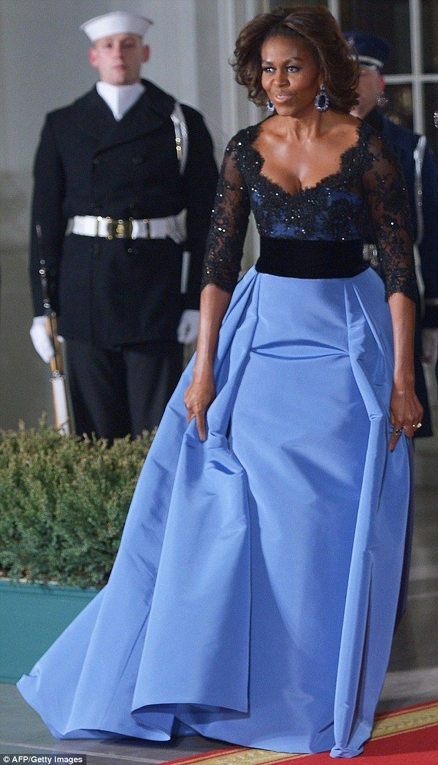 The top went over a blue silk faille corset and long skirt with a train that billowed behind the first lady as she walked with President Bar...