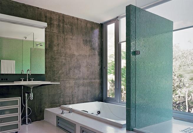 #Bathroom / Impermeabilizadas, as placas de concreto ficaram aparentes em uma das laterais do banheiro da suíte. Junto à janela que ocupa todo o vão, a banheira e o boxe são separados por painel de alvenaria revestido de pastilhas.