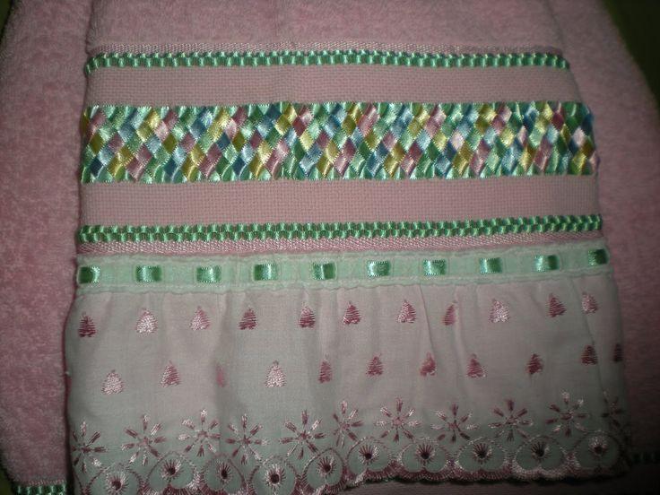 Bordado arco íris em fita de cetim com barrado decorado. <br>Confeccionados em toalha de qualidade - 100% algodão <br>Tamanhos das toalhas: <br>GRANDE: R$ 100,00 <br> - Banho: 1,50x0,90 <br>- Rosto: 0,90x0,50 <br>MÉDIA: R$ 90,00 <br>- Banho: 1,40x0,70 <br>- Rosto: 0,80x0,50