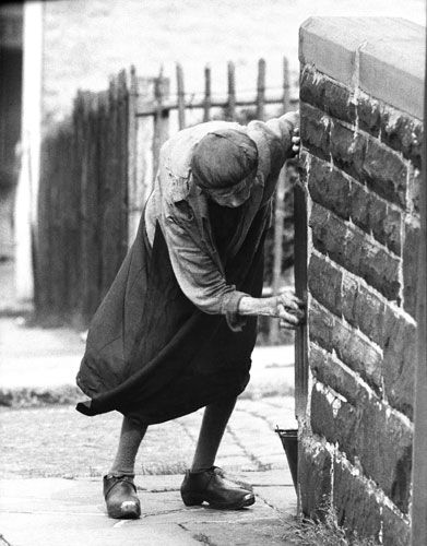 John Bulmer - Nelson, Lancashire (1960)  As the mills closed, many of Nelson's young people moved away, leaving large numbers of middle-aged unemployed people. A woman, still wearing her traditional wooden mill clogs while cleaning a gate post, captures the pride that many older residents still had in the town