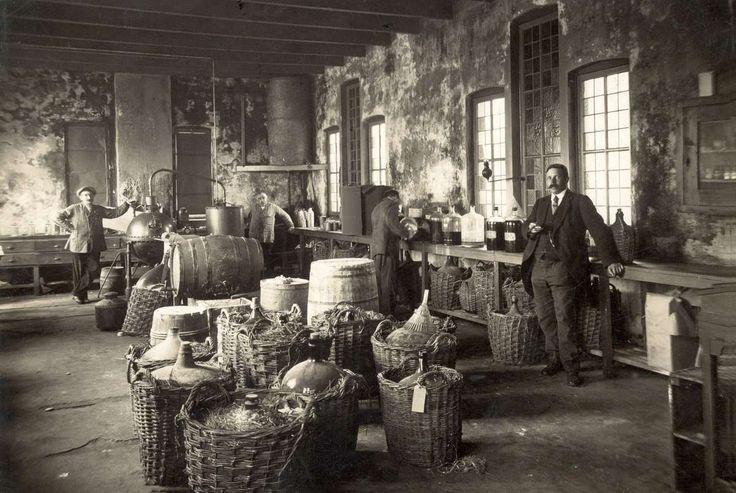 Levensmiddelenfabrieken. Interieur van de Stoom-Essencefabriek Old Holland te Amsterdam met tonnen, kratten en mandflessen en stopflessen op werkbanken, met essences.1917. Nederland