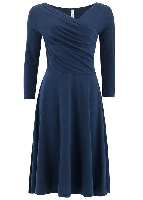 Navy flared jersey dress in certified 100% Fairtrade certified organic cotton. Flared jersey dress with faux wrap panel and 3/4 length sleeve. Also available in bordeaux. Length 102cm.