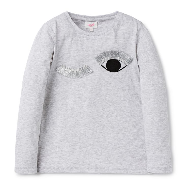 100% Cotton, long sleeve tee. Features placement print eyelashes with iridescent trim. Relaxed fitting silhouette. Available in Cloud