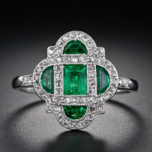 This darling and diminutive early-Art Deco delight - circa 1920 - glistens with a bright-green central emerald-cut emerald and four half-moon emeralds lovingly framed in platinum and teeny-tiny rose-cut diamonds. An original and dreamy Art Deco ring - too delicate for everyday wear. The ring measures about half-an-inch in both directions. 4,850.00