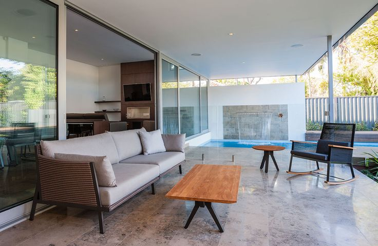 Limstone flooring to the alfresco with featured stone waterfall to the pool designed and built by Urbane Projects, Perth.  Furniture by Mobilia Claremont