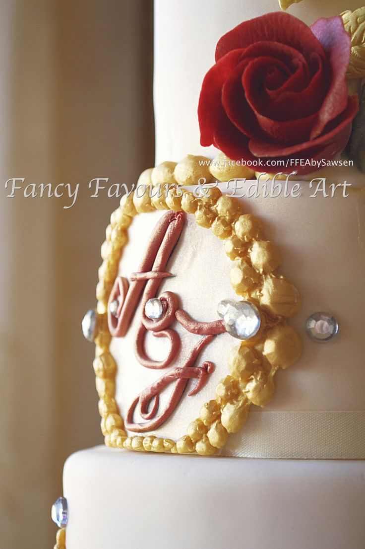 Marsala & Gold Asian/ Indian wedding cake monogram close up | Fancy Favours & Edible Art -- #wedding #cake #Asian #Indian #indianwedding #gold #marsala #red #ivory #lace #tall #jewel #beaded #brooch #jewellery #crystal #vintage #elegant #floral #flowers #rose #freesia #sugarart #sugarflowers #baroque #rococo #moulding #tiered #ornate #fancy #ffeabysawsen #fondant #handmade #custom #customcake #weddingcake #styled #weddingstyle #monogram