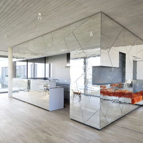 Wrinkly mirrored walls distort the reflection of an apartment interior in Berlin by local architects Lecarolimited