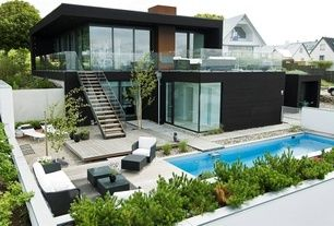 Modern Exterior of Home with Cement wall, Glass panel railing, Outdoor lounge chairs, Exposed staircase, picture window