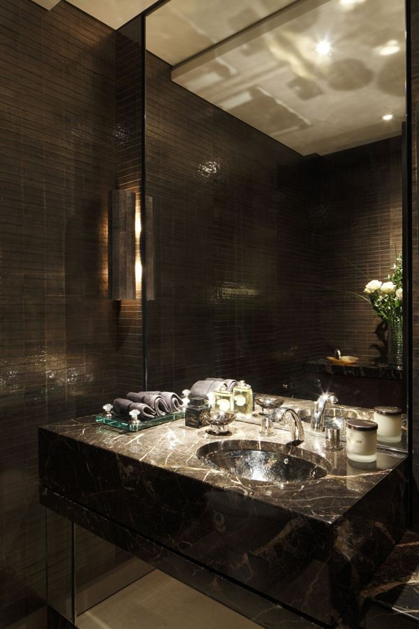 The powder room has been clad in silver & gold-leafed, treated with acid to create a tarnished effect for a more distressed and aged look.