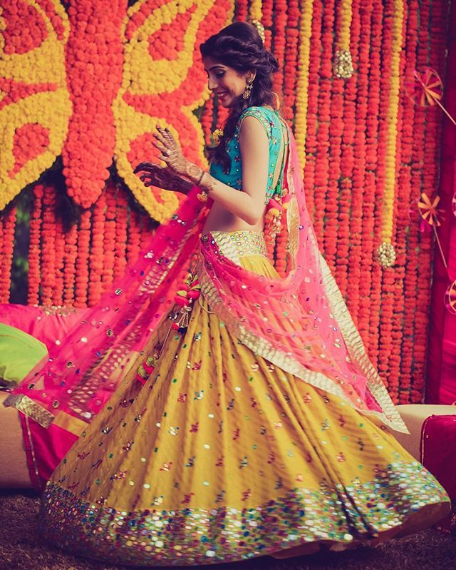 Love the colors in this mehendi outfit by @vaarha | Hair and makeup by @wordshipsalon | photo : @morviimages | #lehenga #twirl #indianbride #bride #yellow #mirrorwork #bridal #wedding #indianwedding #weddings #weddingday #orange #dupatta #indianwear #indianfashion