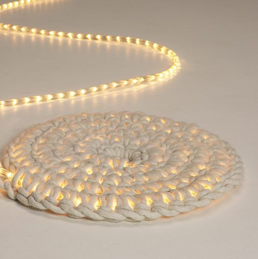 Looks like a standard crochet rug, except instead of a cord in the center, there is a LED rope light. It should follow a 'magic ring' of six stitches, then 12 in the next round, 18 after that, then 24, etc.  In the US, clothes line might be about the right weight to put the whole thing together.