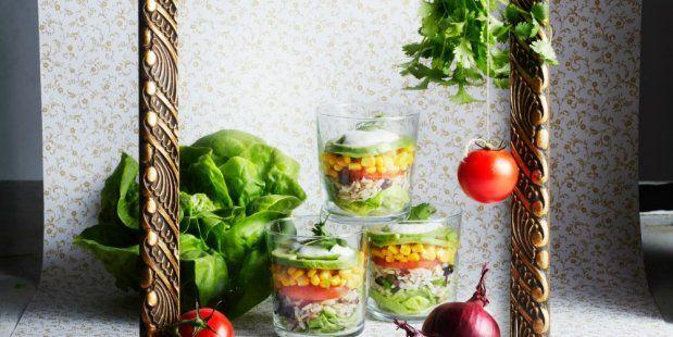 Een recept voor een smakelijke salade met laagjes rijst, ui, zwarte bonen, sla en avocado.