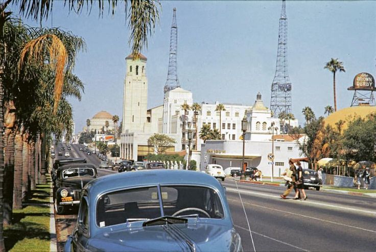 Looking west along Wilshire Boulevard from the curb in front of the Ambassador Hotel, via the Los Angeles Metro Transportation Research Library and Archive (ca. 1945). We can see Brown Derby Restaurant, the Chapman Park Hotel bar, called the Zephyr Room. Beyond the Zephyr is the Cord-Auburn automobile dealership, and past that is the tower of the Wilshire Christian Church. Much farther down Wilshire is the dome of the Wilshire Boulevard Temple. A couple is jaywalking in the middle of…