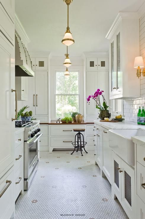 Chic, long kitchen features white cabinets paired with white marble countertops and a white subway tile backsplash illuminated by a row of Gale Petite Hanging Lights. Galley style kitchen boasts a farmhouse sink atop a white hex tiled floor accented with flower mosaic tiles, A stainless steel barrel kitchen hood with brass trim stands over a stainless steel stove next to a white paneled refrigerator.