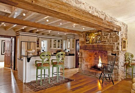 """Pretty cool how they took the fireplace rock and brought it out over the beam. It has a real """"farmy"""" feel with the fireplace practically in the kitchen."""