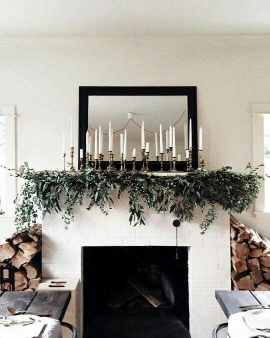 Yule style!! Noel Christmas!! Modern contemporary Farmhouse style!! White painted fireplace with a simple black mirror and garland and a row of silver candlesticks with pure white candles!