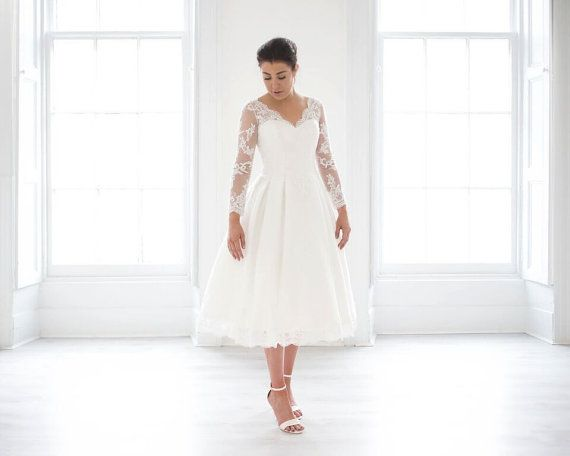 This beautiful wedding dress is made with long sleeves with a tea length skirt.