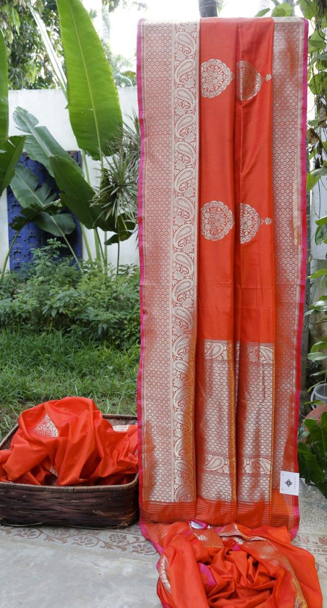 This orange Benares silk has gold zari bhuttas all over. The pallu and border have an intricate weave of gold zari giving it a traditional and classy look