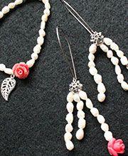 JUEGO PERLAS DE RÍO: Juego pulsera y pendientes en perlas de río color natural, con dijes de rosas rosadas y hojas plateadas; herrajes de los pendientes en acero plateado.