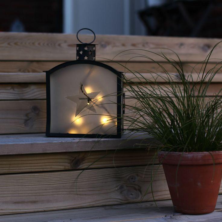 Lanterne LED d'extérieur composée d'une structure rectangulaire en métal noir, de