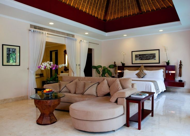 deluxe bedroom with beige sectional sofa and ethnic wooden glass round coffee table and balinese ceiling - Bali Bedroom Design