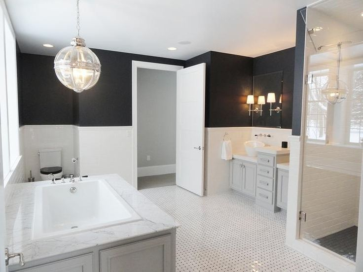 Black and white bathroom features black paint on upper walls and white tiles on lower walls lined with his and hers gray washstands stopped with asymmetrical bowl sinks under frameless mirrors illuminated by Bryant Sconces separated by cabinets alongside a black and white marble tiled floor.