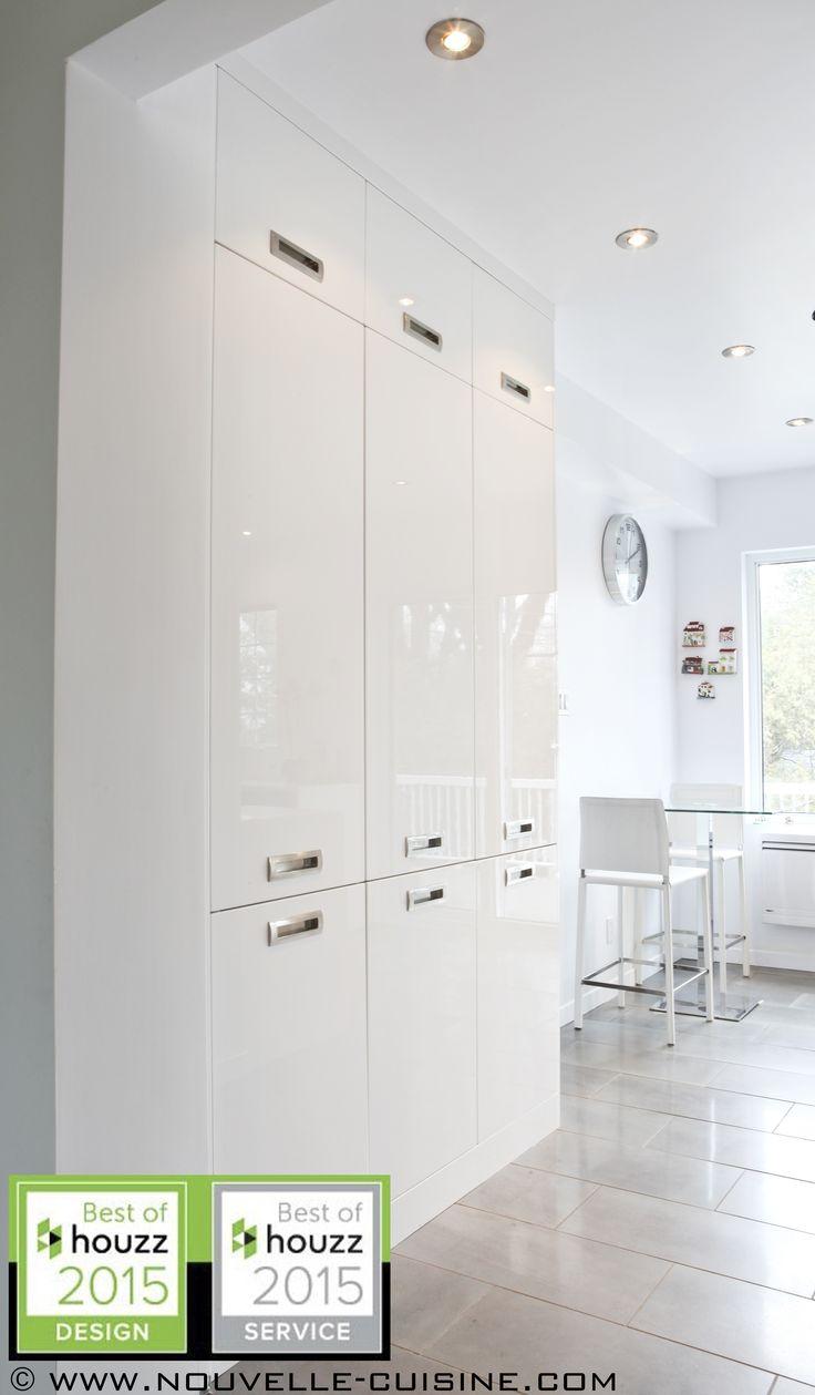 White kitchen cabinets with a glossy finish. / Des armoires de cuisine blanches avec un fini lustré.