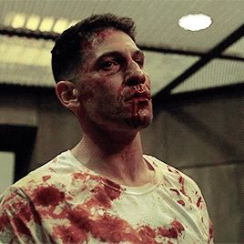 The officers dragged a bloody Frank Castle out of the cell block and into an empty, dark room
