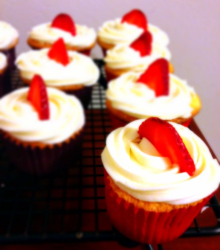 Strawberry filled butter cake cupcakes with cream cheese frosting and strawberry garnish